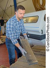 Man lifting plank of wood