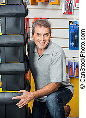 Man Lifting Stacked Toolboxes In Hardware Shop