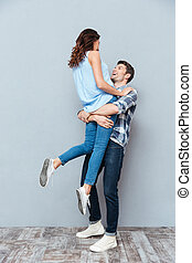 Man lifting up his girlfriend on gray background