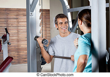 Man Lifting Weights While Looking At Instructor