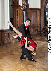 Man Lifting Woman While Performing Tango In Restaurant