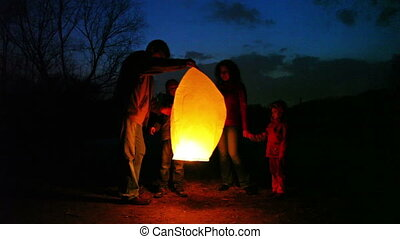 man lifts glowing chinese lantern, its wife joking forces hands air, son and daughter look, part1