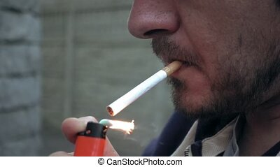 Man lighting a cigarette outdoors