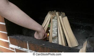 Man lighting up wood piece preparing bonfire outside for...
