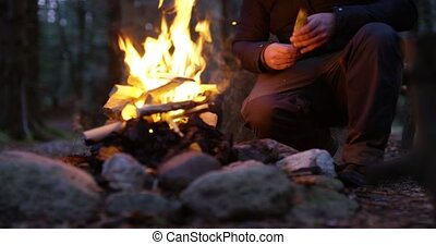 Man lights a campfire outdoors in the forest - Man with...