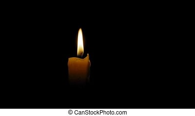 man lights a candle in the dark with matches, close-up