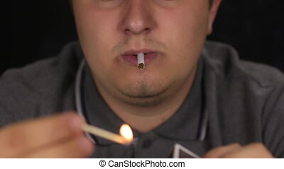 Man lights a cigarette using a wooden match.