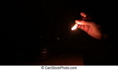 man lights a kerosene lamp