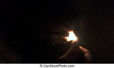 Man lights a match in darkness and burning on black background.  slow-motion