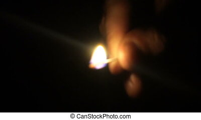 Man lights a match in darkness. Slow Motion