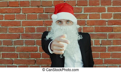 man like a Santa Claus chooses and shows with his index finger to the camera, Merry christmas and New year 2019, red brick wall as background