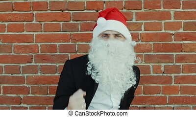 man like a Santa Claus is dancing, Merry christmas and New year 2019, red brick wall as background