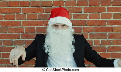 man like a Santa Claus is dancing, Merry christmas and New year, red brick wall as background