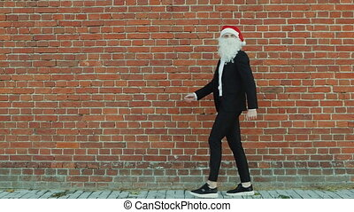 man like a Santa Claus walks along a wall, Merry christmas and New year, red brick wall as background