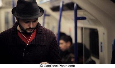 Man listening music on a tube train
