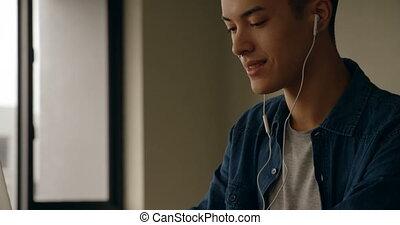 Man listening music while using laptop at home 4k