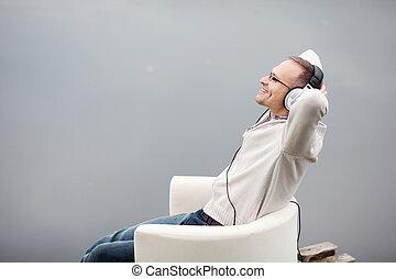 Man Listening Musing Through Headphones On Pier - Portrait ...