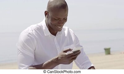Man listening to music on cell phone while seated