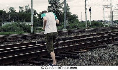 man listening to music on earphones and inattentively crosses a railway or railroad, life threatening