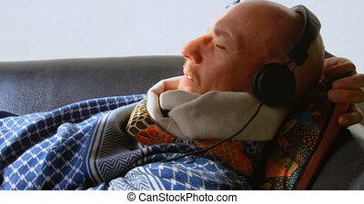 Man listening to music on headphones 4k