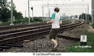 man listening to music on headphones and inattentively crosses a railway or railroad, life threatening