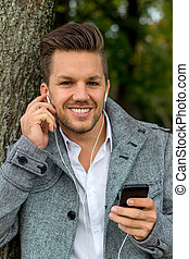 man listening to music on mobile phone - a man listening to ...