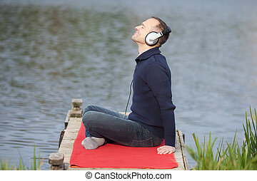 Man Listening To Music On Pier Against Lake