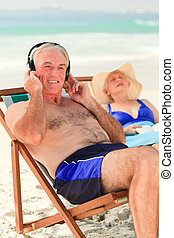 Man listening to music while his wife is sleeping