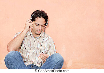 man listening to music with earphones and personal stereo