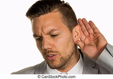 man listening to - a man holds his hand to his ear