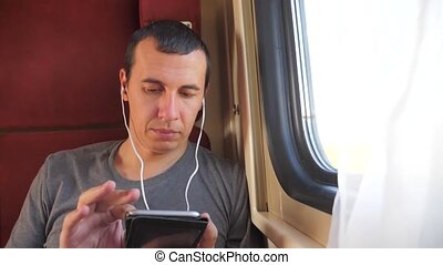 man listening to the music on the train journey rail car...