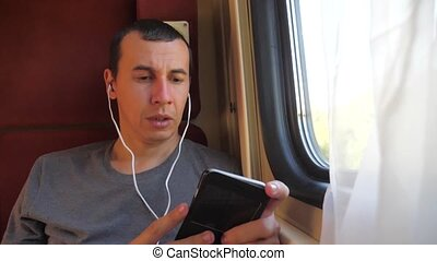 man listening to the music on the train rail car coupe...