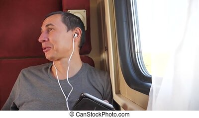man listening to the music on the train rail car lifestyle...