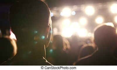 Man listens the rock concert in stadium, music light show