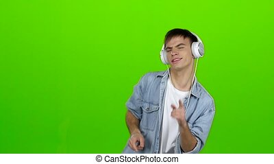 Man listens to energetic music in headphones and dances. Green screen. Slow motion