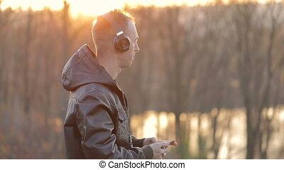 Man Listens to Music near Lake