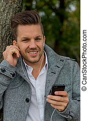 man listens to music on mobile phone - a man listens to ...