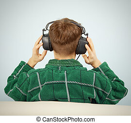 A young man listens to symphonic music at home on the couch