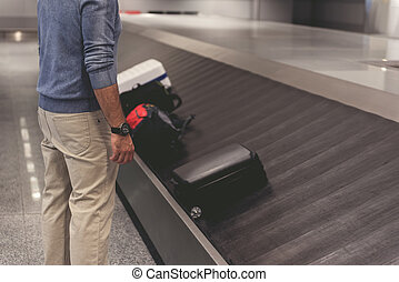Man locating near luggage at terminal - Tourist is standing ...