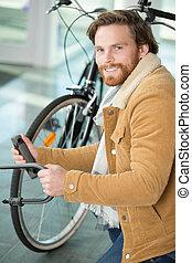 man locks bicycle lock on bicycle parking