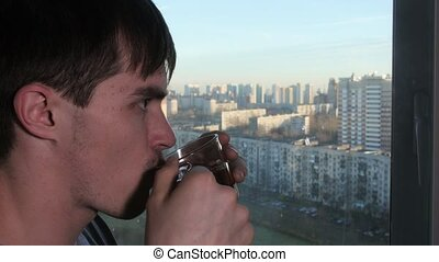 Man look at window home and drink hot tea
