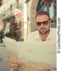 Man look through map in summer city