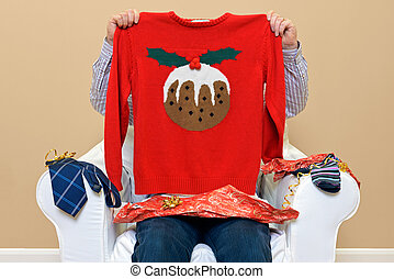A man opening Christmas presents to discover he got a Christmas themed jumper to go along with the usual socks and tie.
