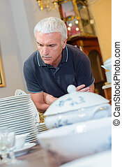 Man looking at antique crockery