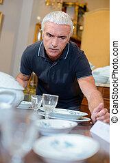 Man looking at antique crockery