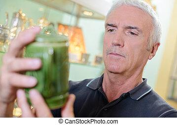 Man looking at antique pot