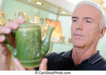 Man looking at antique tea pot