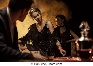 Man looking at beautiful woman sitting on poker table in casino