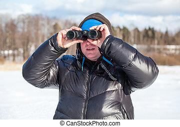 Man looking at binocular in warm winter clothes outdoor