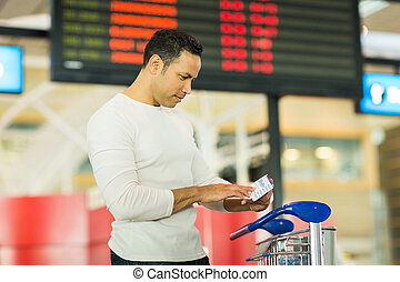 man looking at boarding pass at airport
